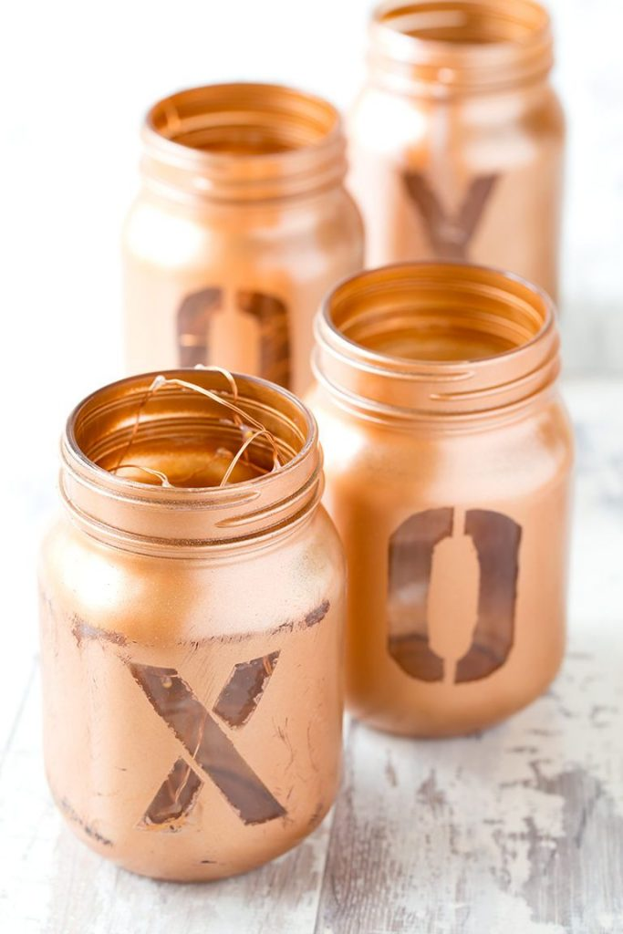 If you have a number of mason jars empty in your pantry too, why not give a few coats of copper paints to spell out a message with washi tape or masking tape.